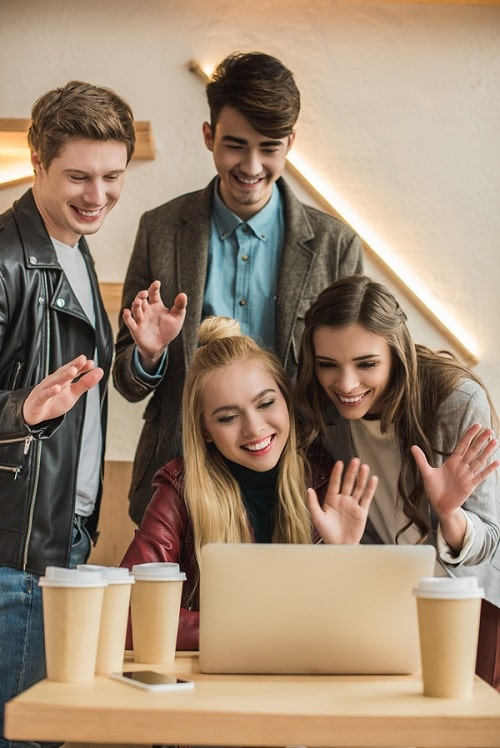 A group of friends at a coffee shop, waving at a computer screen during a video chat.