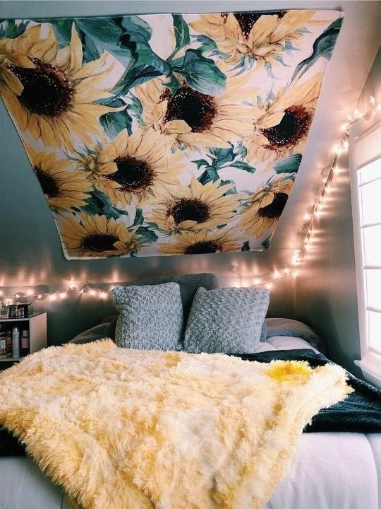 A fall-inspired dorm room with a sunflower tapestry and matching furry yellow throw blanket.