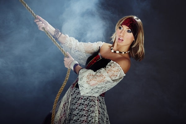 A woman in a swinging sailor fashionista pirate costume.