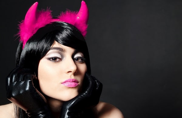 A woman wearing a pink devil costume with pink horns, pink lipstick, and black leather gloves.
