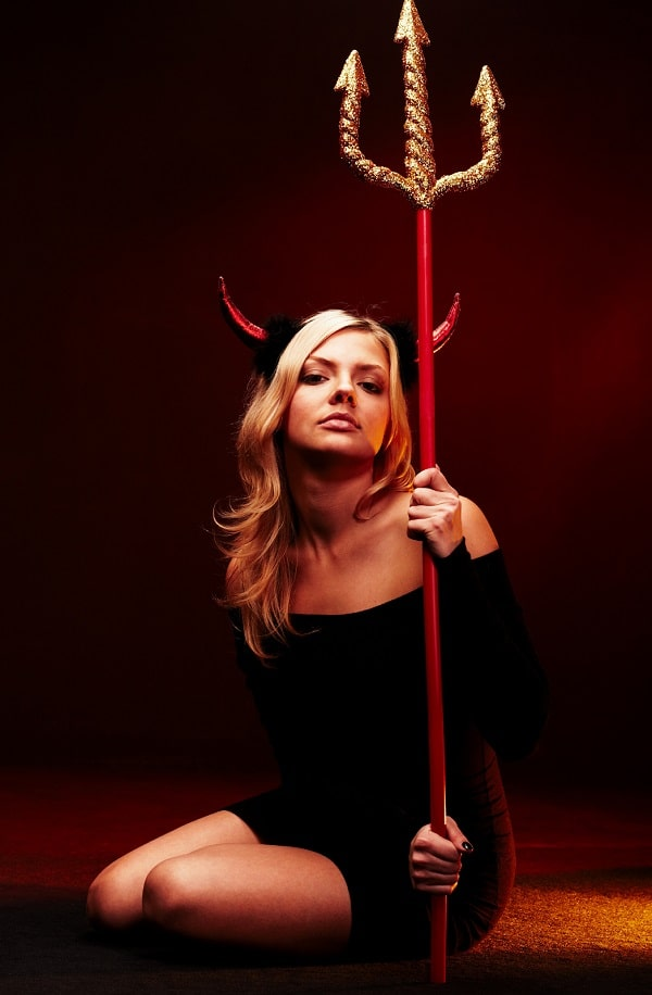 A blonde-haired woman in a golden lady devil costume, wearing a black dress, metallic red devil horns, and a gold pitchfork.