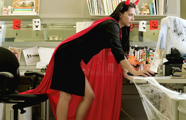 A woman wearing a devil costume in the office, with a red cape, black corporate attire, and devil horns.