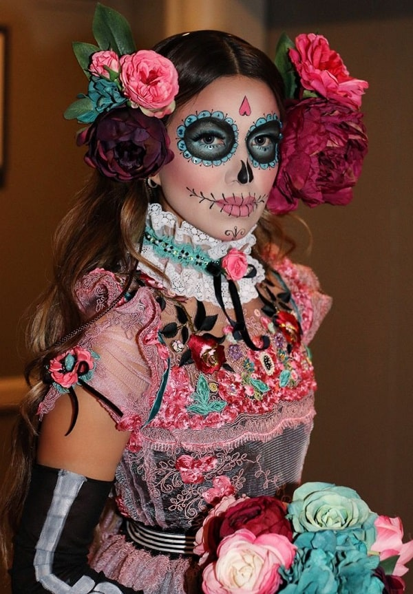 A woman in a Day of the Dead costume, wearing a colorful peasant dress with a lace collar and vibrant face paint.
