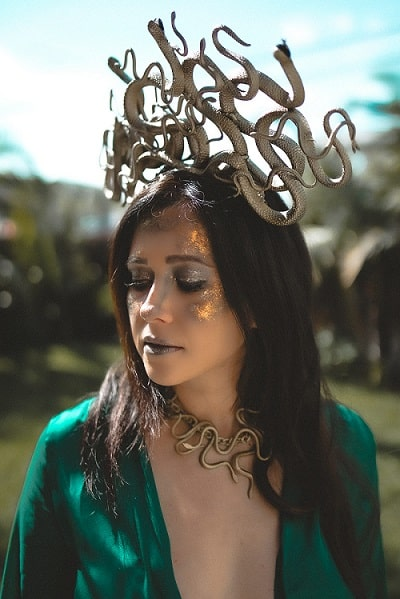 A dark-haired woman in a Medusa costume with a blue-green dress, gold choker, and gold headdress with snakes.