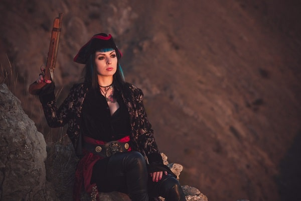 A woman wearing a pirate costume, holding a gun and sitting at the beach.