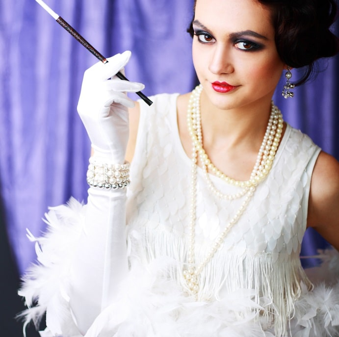 A woman in a white flapper girl outfit with matching pearls and cigarette holder.