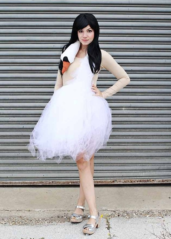 A woman in a white swan dress costume made of white tulle and a swan's head hanging over the neck and shoulder, with a skin-tone bodysuit underneath.