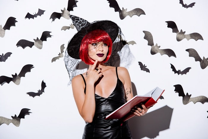 A woman in a witch costume, wearing a vibrant red wig to match her all-black outfit.