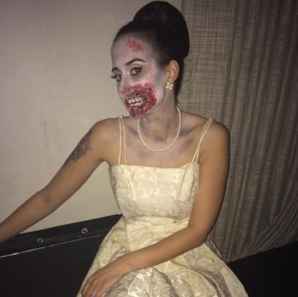 A woman in a zombie bride costume, wearing a white strapless gown and fake blood face paint.