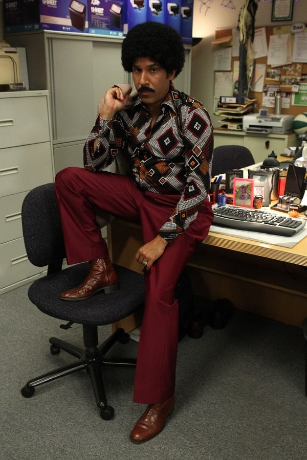 Oscar Martinez in a 1970s costume, wearing bell-bottom jeans, a printed shirt, and brown boots.
