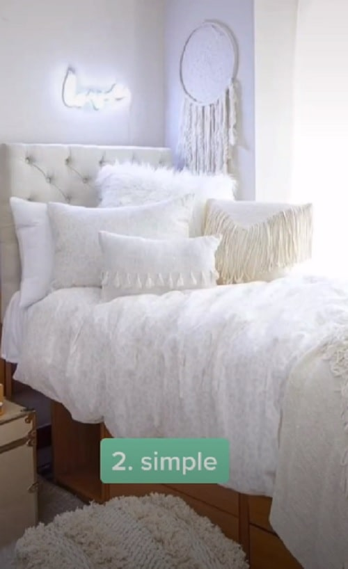 """An all white dorm room aesthetic with white pillowcases, white throw pillows, and a """"love"""" neon light wall hanging decor above the bed."""