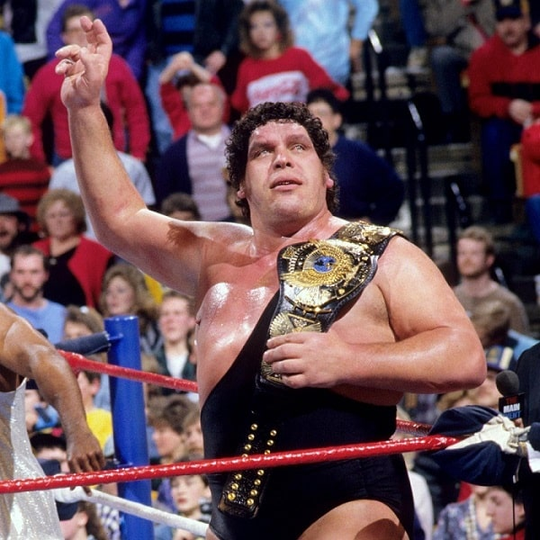 André the Giant in his wrestling singlet, holding his championship belt and waving to the crowd.