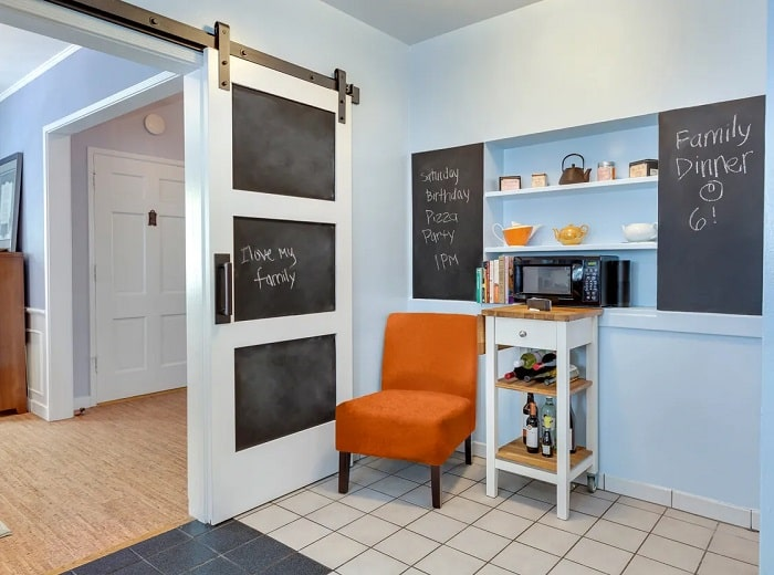Blackboards with chalk writing on them, put together to serve as a useful dorm room divider.