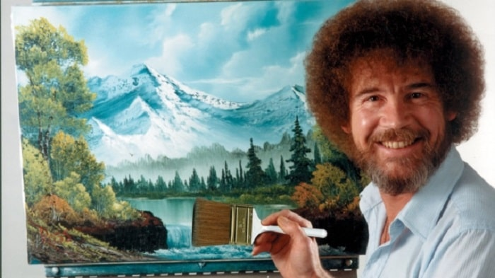 Bob Ross and his signature mustache and curly hair while holding a paint brush in front of a finished painting.