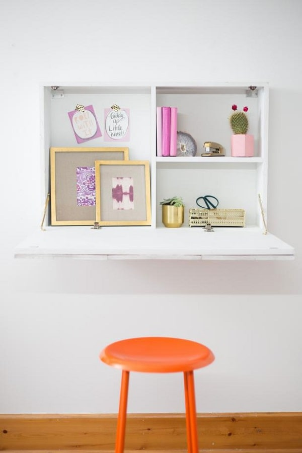 Four shelves built into a murphy table with a matching orange backless chair.