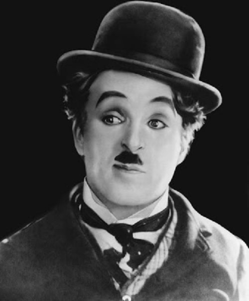 A black and white photo of the iconic Charlie Chaplin, with his signature mustache, suit, and bowler hat.