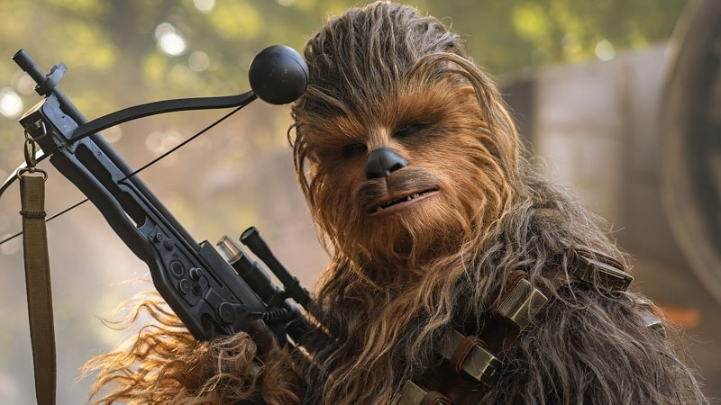 Chewbacca from Star Wars, holding his weapon and poised for action.