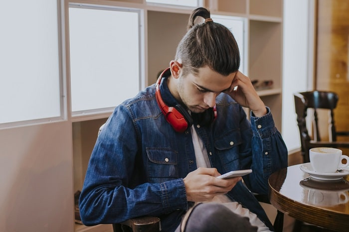 A college guy in a denim jacket looking at his smartphone and wearing a pair of red headphones around his neck, with a cup of coffee beside him.