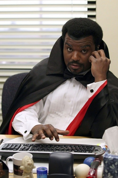 Darryl Philbin in a Dracula costume, wearing a white shirt and black cape with red trim.