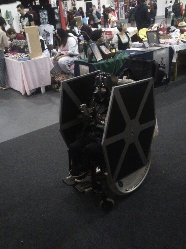 A man in a Darth Vader costume, riding his improvised TIE Fighter at a comic con.
