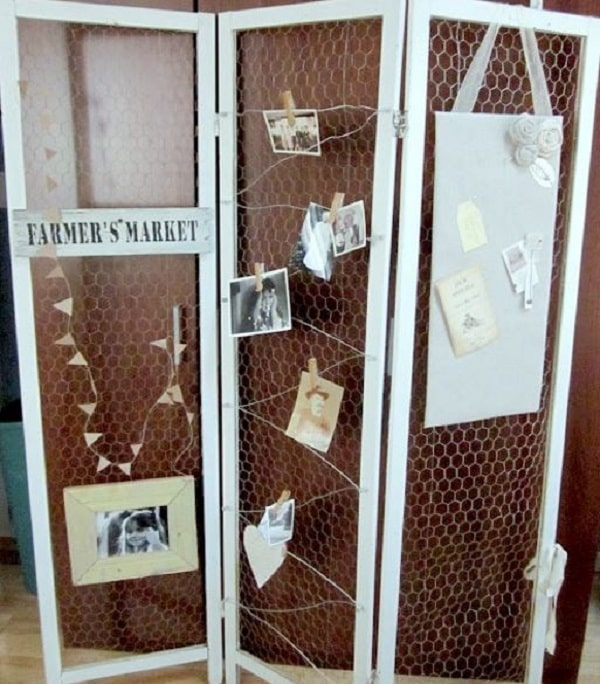 A DIY chicken-wire screen dorm room divider made of a metal-framed panel room divider and some chicken wire net put together for hanging photos and various objects.