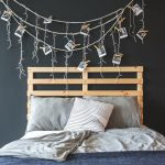 A bed with a wooden frame and a DIY fairy light picture wall hanging above it.