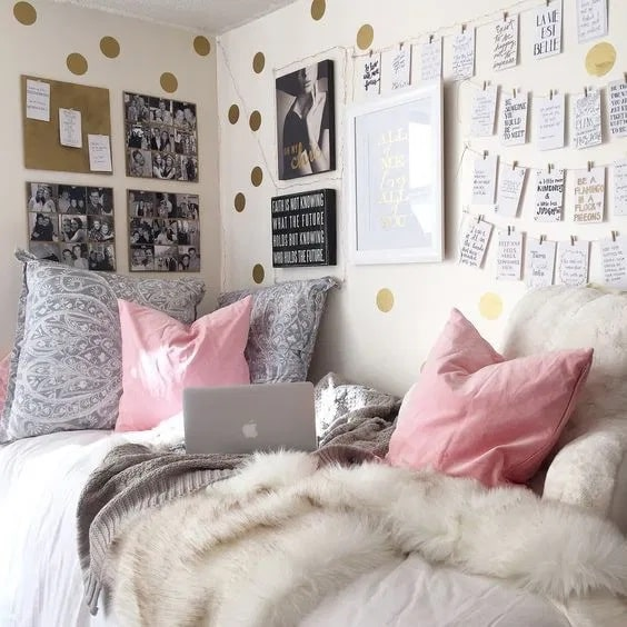 A dorm room wall adorned with metallic gold decal dots and a corkboard for hanging up notes.