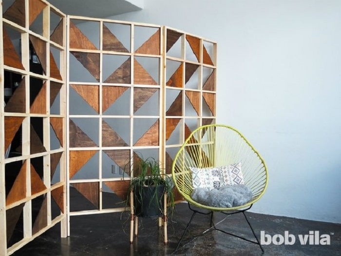 A DIY dorm room divider made of triangular pieces of plywood put together and stained with different shades of brown.