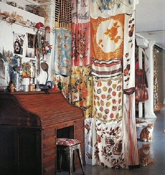 A DIY cloth draping for a dorm room divider made of printed satin and silk scarves put together.