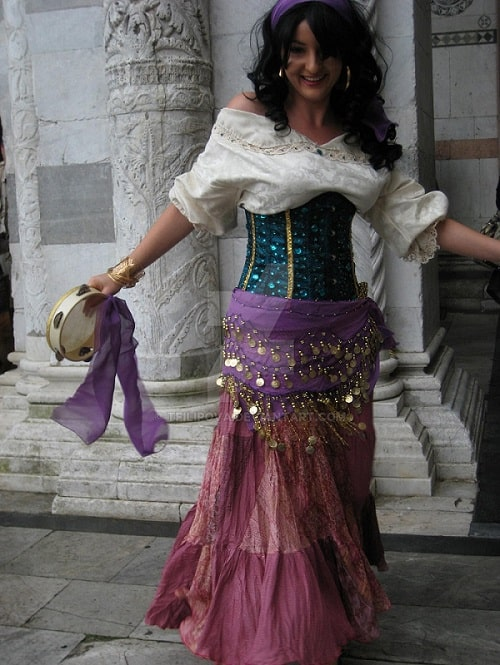 A woman dressed as Esmeralda, with her white ruffled top, sequined corset, flowy skirt, and sequined belly dancing scarf wrapped around her waist.