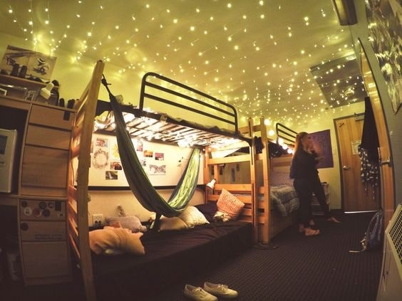 A dorm room with fairy lights on the ceiling and a green hammock tied to the bedposts.