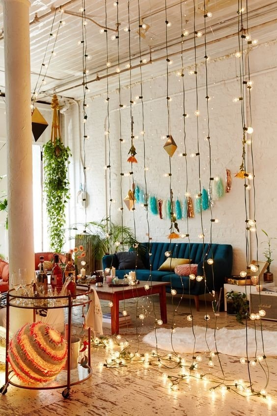 Outdoor globe string lights hanging from the ceiling to serve as a dorm room divider, with a bar cart near it the living room.