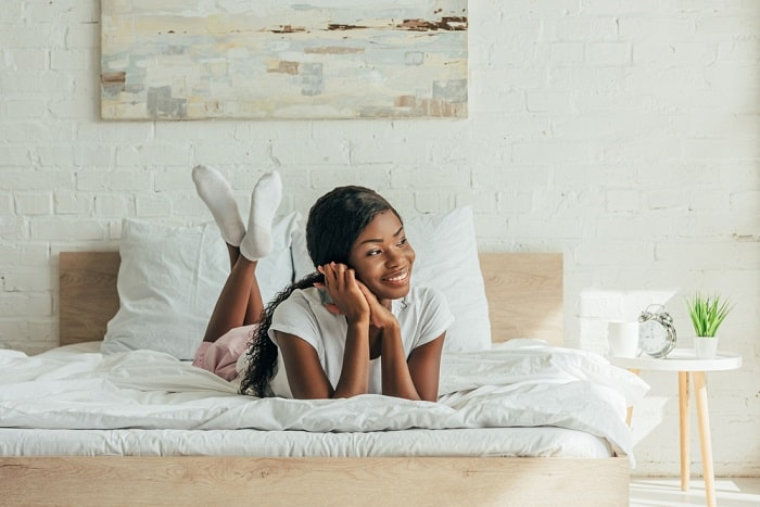 A girl smiling on her bed with a wooden headboard and white sheets plus a wall art hanging above it.