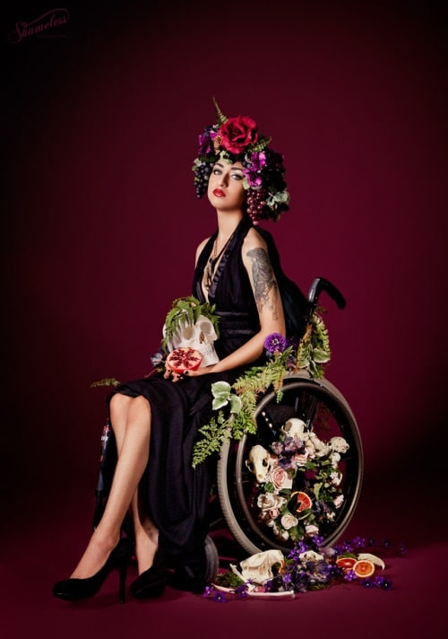 A woman in a flower queen costume, with her wheelchair adorned with various flower garlands and her hair adorned with a flower crown.
