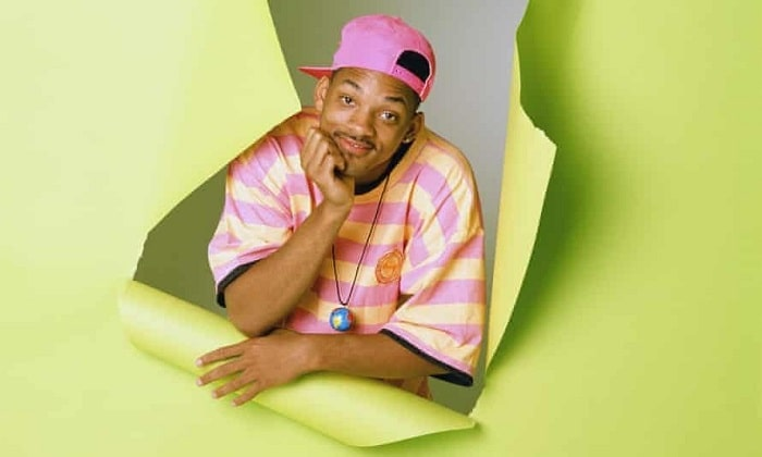 Will Smith as The Fresh Prince of Bel-Air, wearing his neon-colored striped shirt with matching sideways-worn baseball cap.