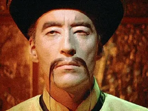Fu Manchu with his signature full, straight mustache in two tapered tendrils extending past the jawline, wearing a yellow kung fu shirt