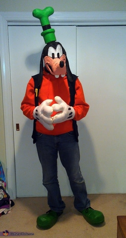 A man in a Goofy costume, wearing an orange long-sleeved shirt with green top hat and long black ears.