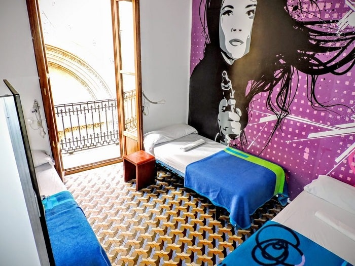 A three-person hostel room with large wall graphics and matching patterned floor with a loud, clashing design.
