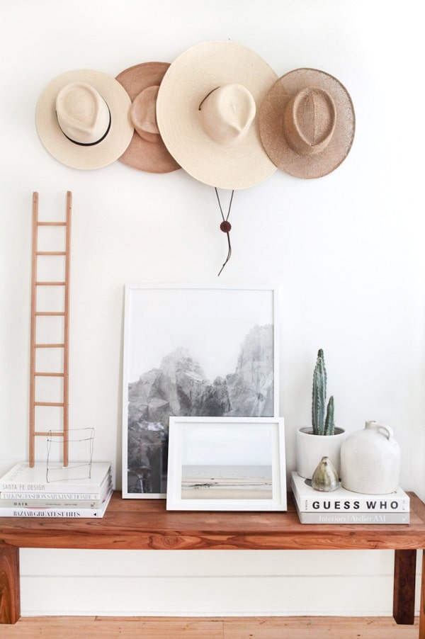 A dorm room hat wall using various wide-brim straw and summer hats hung on a wall rack.