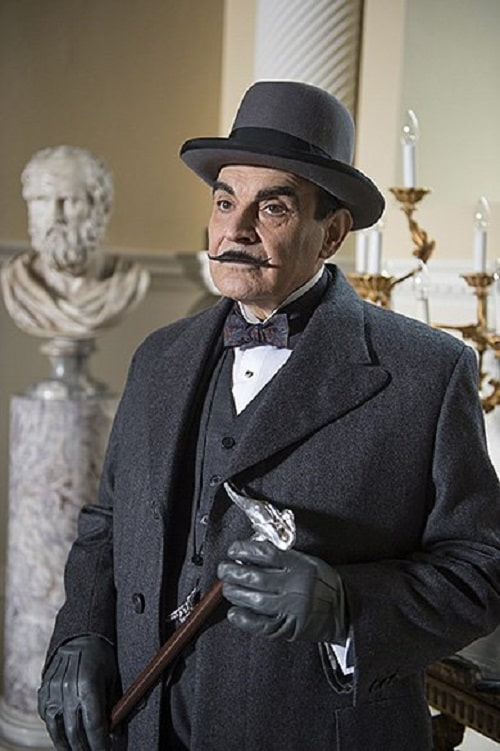 Hercule Poirot with his signature pointy mustache, wearing a three-piece suit and shooting gloves, while holding a wooden walking stick with a sterling silver bird handle.