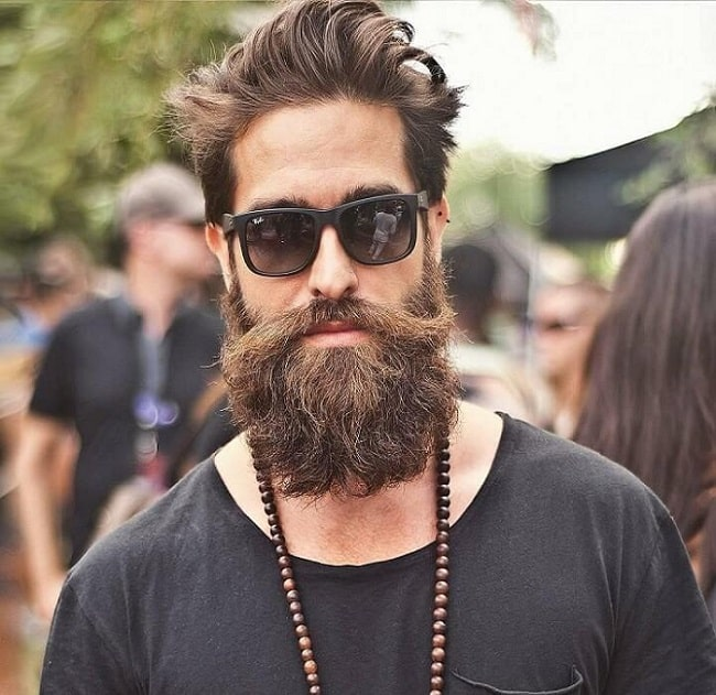 A hipster guy with a full beard, dark sunglasses, and bead necklace.