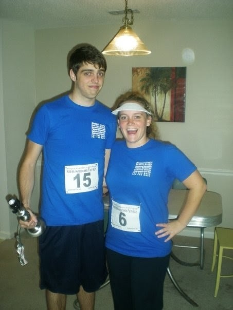 A man and a woman in a Jim-and-Pam-after-the-fun-run costume, wearing their blue cotton shirts, race numbers, and a white sun visor.