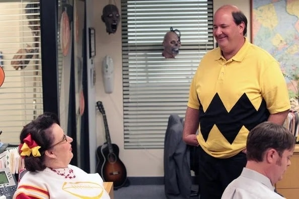 Kevin Malone in a Charlie Brown costume, wearing an improvised yellow shirt with a black zigzag cutout attached to it.