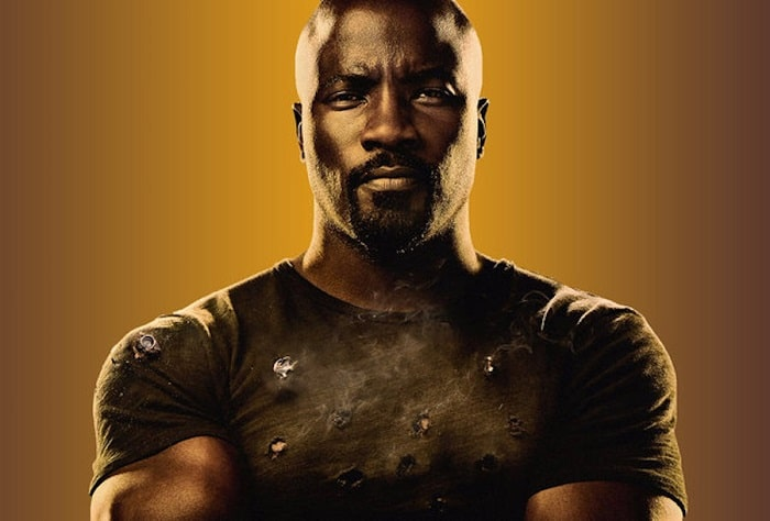 Luke Cage with his bald look and full beard, wearing his tight-fitting dark green shirt with bullet holes.