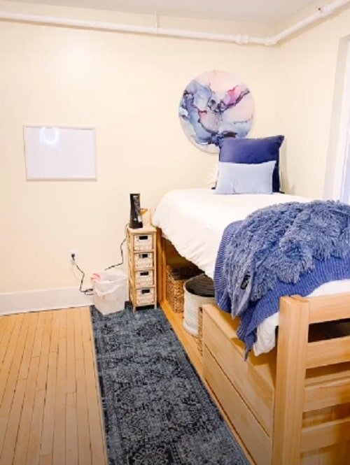 A dorm room with marble wall art hanging above the bed and matching throw pillow covers plus throw blanket.