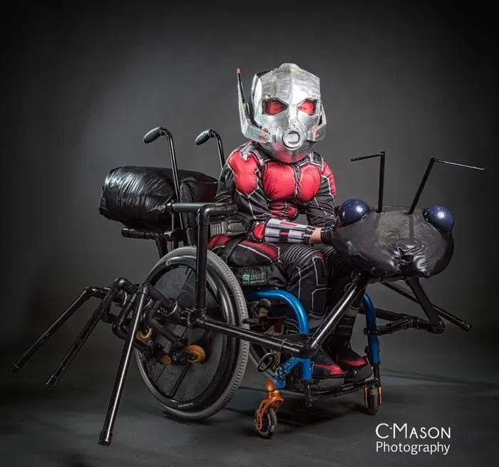 A man in an Ant-Man costume, with his wheelchair dressed as an ant with legs made of pipe fittings and body parts made of bean bag fillings wrapped in plastic bag.