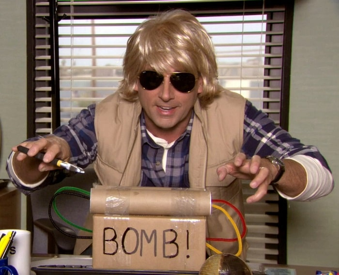 Michael Scott dressed as MacGruber, wearing his blond mullet wig, safari vest, and aviator shades.