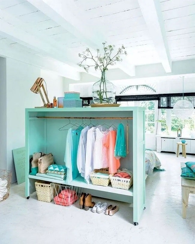 A DIY middle-of-the-room closet and dorm room divider made of an open-style wooden cabinet with a curtain rod installed and uniform hangers to hang the clothes.