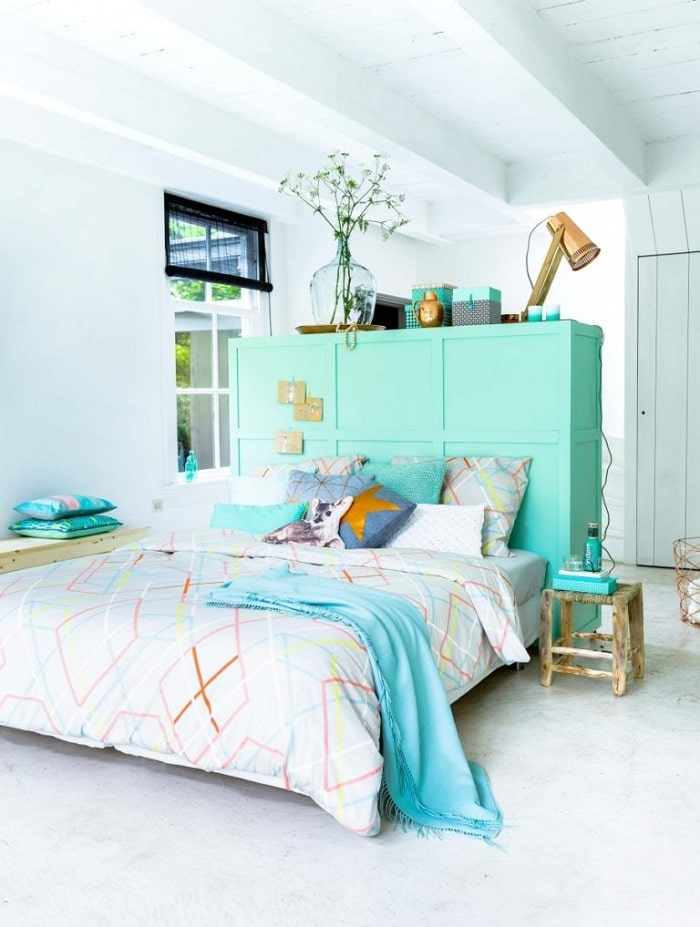 A DIY dorm room divider made of headboard furniture painted a teal shade and placed in the middle of the room.