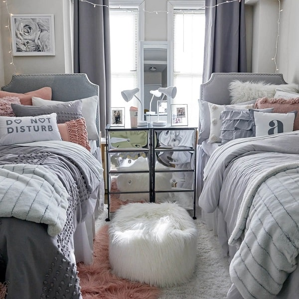 A dorm room with a mirrored side table and furry ottoman between two beds with pink and gray beddings.